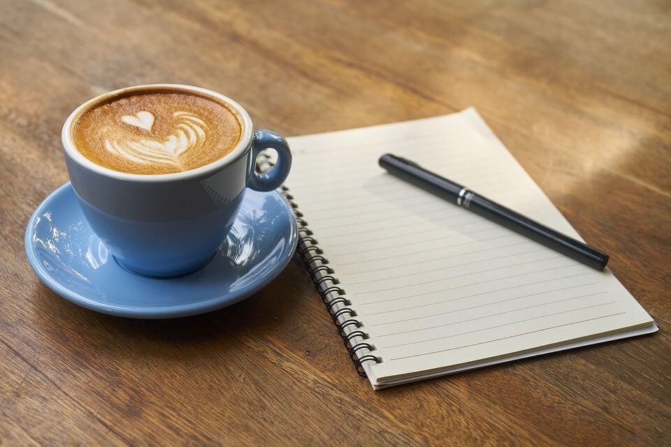 copo de cappuccino com agenda e caneta ao lado