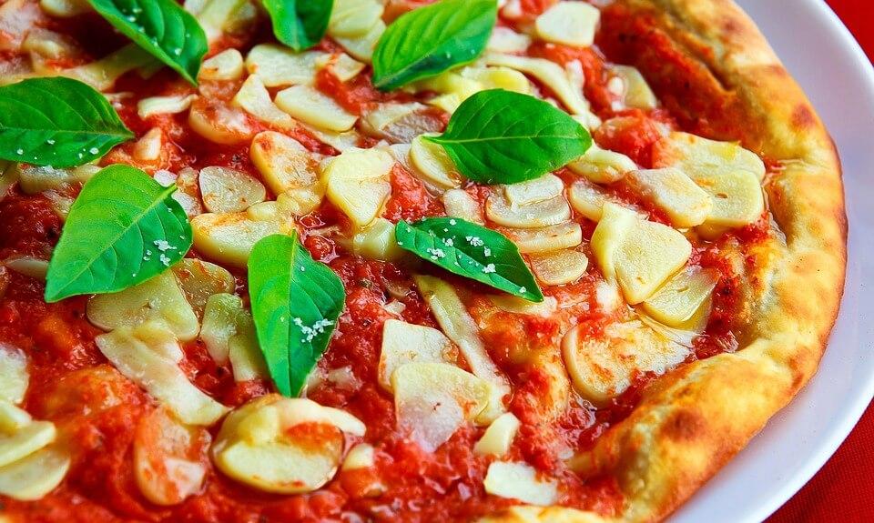 prato de pizza italiana com manjericão e pedaços de alho