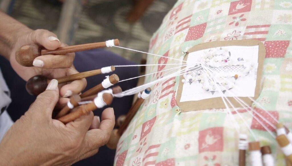 mãos bordando tecido