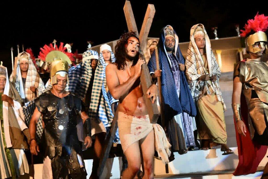 encenação de Jesus Cristo carregando cruz com várias pessoas ao redor