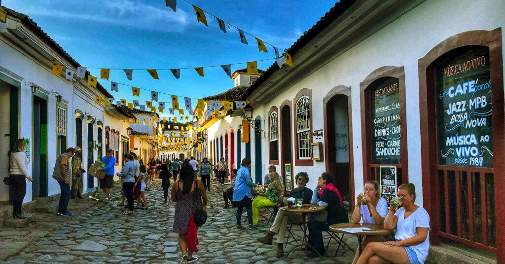 casas antigas, pessoas na rua, bandeirinhas penduradas no centro histórico de Paraty